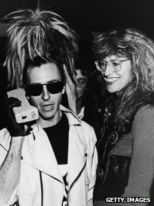 A member of Sigue Sigue Sputnik makes a telephone call, accompanied by Janet Street Porter