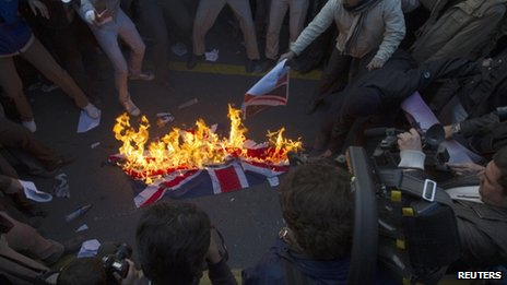 Protesters burn a British flag taken down from the British embassy in Tehran November 29, 2011.