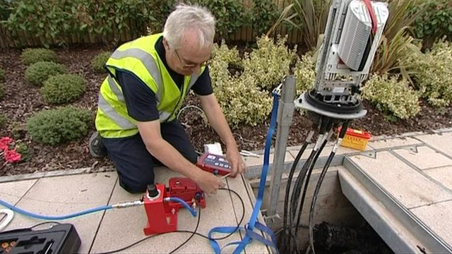 Workman installing cables under pavement