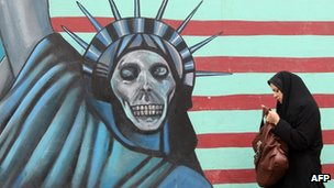 An Iranian woman walks past an anti-US mural painted on the wall of the former US embassy in Tehran on 19 November  2011