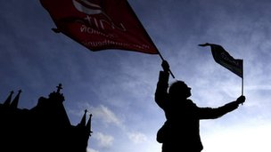 A public sector worker waves flags during a rally in Bradford City centre.