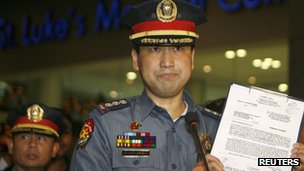 Senior Superintendent Joel Coronel shows the arrest warrant served on former Philippine president Gloria Macapagal Arroyo on 18 November 2011 