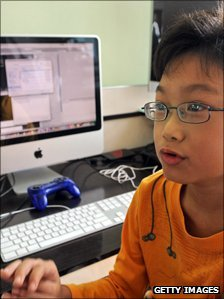 Boy sits by computer