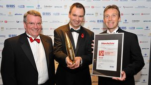 Three men from the Cosworth Group celebrate