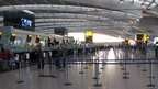 "Passengers check in at quiet desks in Heathrow Airport""s Terminal 5"