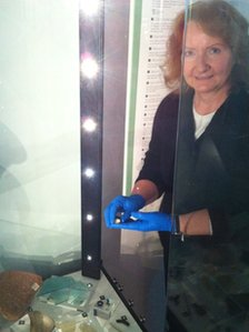 Gill Levy adds a Roman ring to a display case at the Winding House museum