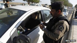 A Saudi policeman checks a driver in Saudi Arabia's eastern Gulf coast town of Qatif 25 November 2011