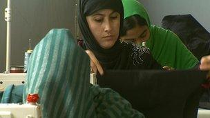 Women working at a textile factory near Kabul, alongside men