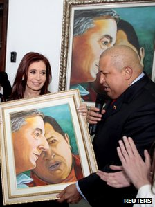 Hugo Chavez (right) presents Argentina's Cristina Fernandez with a painting he did of himself and her late husband Nestor Kirchner