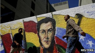 People walk past a mural depicting South American independence hero Simon Bolivar in Caracas