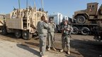 US soldiers next to trucks loaded with military vehicles and equipment as part of preparations to leave their military base at Camp Victory (20 November 2011)