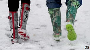People in colourful wellies walking in the snow