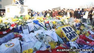 Fans gather as floral tributes are left to Gary Speed at the foot of the Billy Bremner statue outside Leeds United's Elland Road