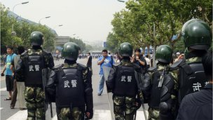 Paramilitary police stand guard as hundreds of people protest in Dalian