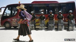 A woman walks past police in Cajamarca during a strike against the Conga gold mine project - 25 November 2011