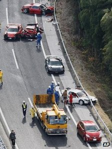 Police officers inspect damaged Ferrari cars on the Chugoku Expressway in Shimonoseki, southwestern Japan, 4 Dec 2011