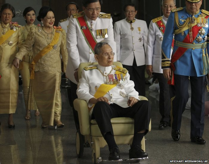 Thailand's King Bhumibol Adulyadej (centre), is pushed on a wheel-chair as he leaves Siriraj hospital to the Grand Palace for a ceremony celebrating his birthday in Bangkok