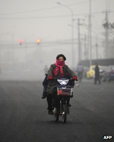 A resident wearing a scarf over her mouth rides a bicycle in Beijing on 5 December 2011
