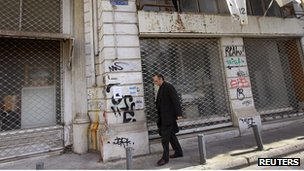 A man walks past shops, which have been closed since last year, in central Athens October 27, 2011.