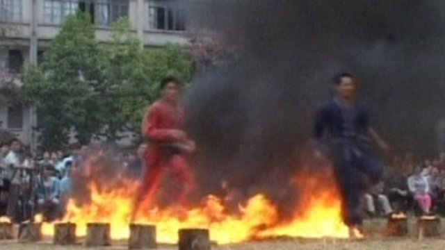 The Chinese ethnic athletes are running through fire at the sports festival.