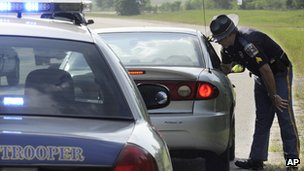 A police man talks to a driver in a vehicle. The police cruiser is in the foreground.