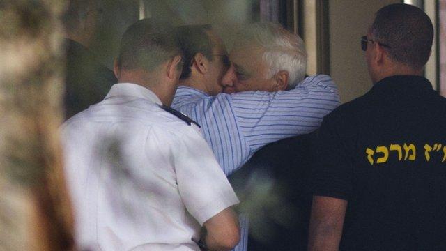 Former Israeli President Moshe Katsav hugs his son as he enters Maasiyahu prison