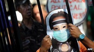 A protester wearing a mask carrying the image of former Philippine president Gloria Arroyo in Manila on November 29