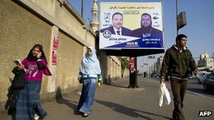 Egyptians walk past a poster for two Freedom and Justice Party candidates in Cairo (5 December 2011)