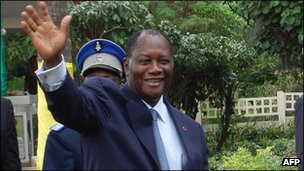 Ivorian President Alassane Ouattara waves to the crowd