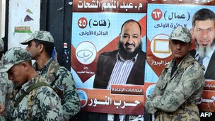 Egyptian soldiers stand in front of campaign posters for candidates from the hardline Islamist Salafist Al-Nur Party, in the coastal city of Alexandria on 5 December 2011.