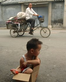 A young girl sits in a cardboard box on the edge of a road in Beijing (file photo)