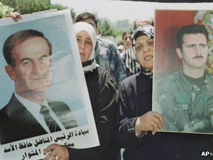 Syrian women carry portraits of Hafez and Bashar Assad Bashar in Damascus in June 2000.