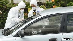 Forensic workers examine the car of Alfredo Landaverde who was shot dead on Wednesday
