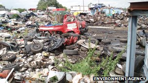 Large piles of scrap metal and tyres at a waste dump