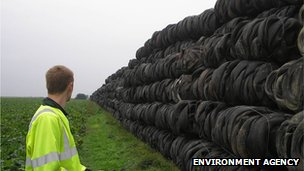 An Environment Agency officer looks at a huge line of tyres as far as the eye can see