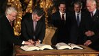 British PM Gordon Brown (second left) signs Lisbon Treaty next to (centre to right) European Commission President Jose Manuel Barroso, Portuguese Prime Minister Jose Socrates and European Parliament President Hans-Gert Poettering in the Coche museum in Lisbon (13 Dec 2007)