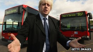 London Mayor Boris Johnson in front of two bendy buses