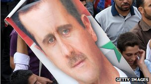 Demonstrators hold up a poster of President al-Assad