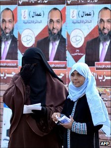 An Egyptian woman wearing a full face veil and a girl stand by campaign posters for a candidate from al-Nur
