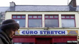 A woman walks past a vacant discount shop in the village of Buncrana in County Donegal