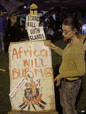 Protester holding a night-time vigil outside the conference hall, Durban (Image: AP)