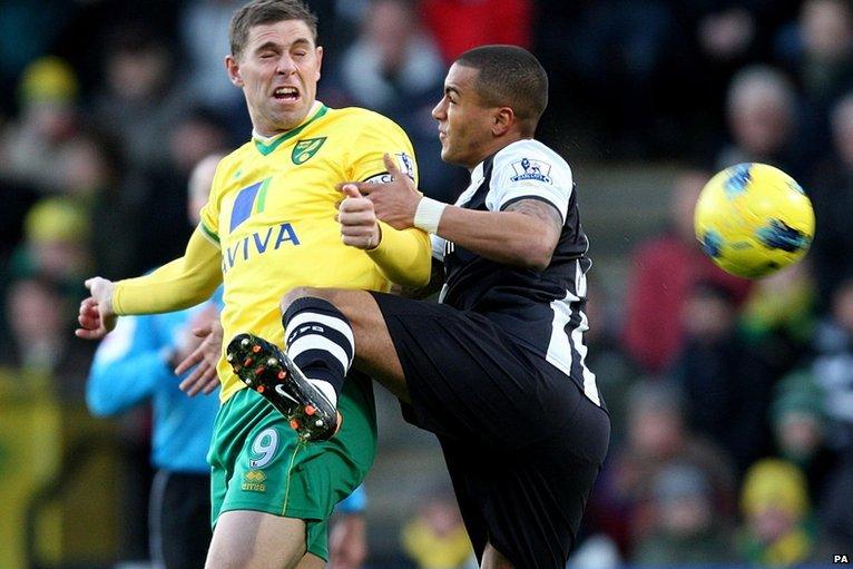 Grant Holt (left) and Danny Simpson challenge for the ball