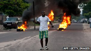 A supporter of DR Congo's opposition leader Etienne Tshisekedi reacts in front of burning tyres as he demonstrates in Kinshasa on 9 December