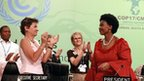 South African Foreign Affairs Minister and President of the 17th Conference of the Parties Maite Nkoana-Mashabane (R) receives a standing ovation from Congress of Parties ( COP17) Executive Director Christiana Figueres and hundreds of delegates at the closing plenary on the final day of negotiations of the COP17 Climate Change Conference at the International Convention Centre in Durban