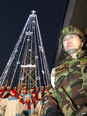 South Korean military officer stands guard as Christians prepare a lighting ceremony of a tree near the border with the North in December 2010