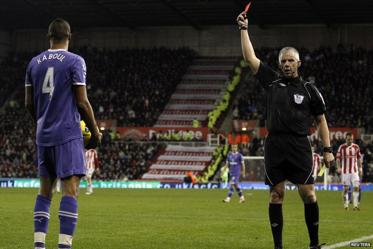 Referee Chris Foy shows Younes Kaboul a red card