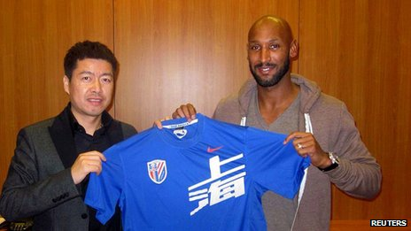 Anelka (r) poses with Shanghai Shenhua shirt