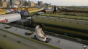 A trucker prays on top of an idle oil tanker in the Pakistani port of Karachi, 7 December