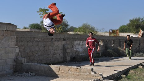 Mohammed Jamal Jahbir jumps in the air, followed by Abdullah Mamoun and Jihad Abu Sultan in Khan Younis