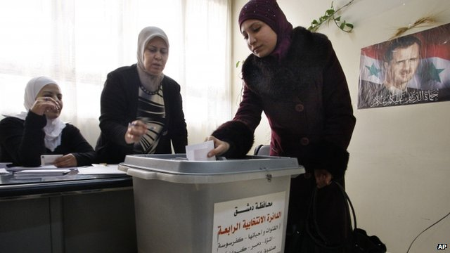 A woman casts her vote in Damascus, Syria